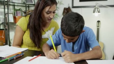 A mother sits beside her son, helping him to draw and write — Stock Video