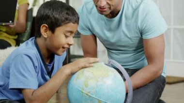 Father and son using a globe to look at countries around the world — Stock Video