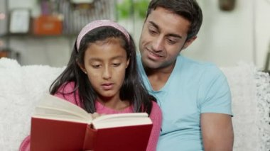 A father and his daughter spending time together at home, reading a book — Stock Video