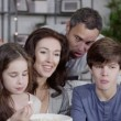 Happy family watching tv together and eating popcorn — Stock Video #45259535