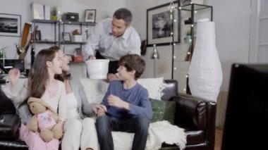 Family eating popcorn while watching tv — Stock Video