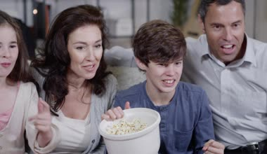 Happy family watching sports on t.v. and spilling popcorn everywhere — Stock Video