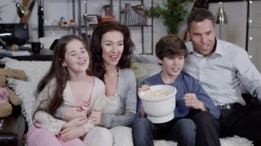 Happy family watching sports on tv and spilling popcorn everywhere — Stock Video