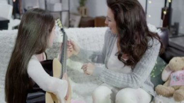 Mother and daughter spending time together and playing the guitar — Stock Video