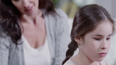 Loving mother plaiting her daughter's hair and gives her a kiss — Stock Video