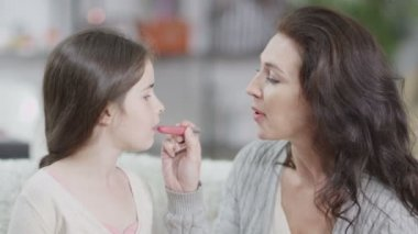 Attractive woman teaches her daughter how to put on lipstick — Stock Video
