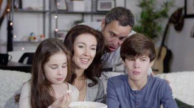 Mutlu aile birlikte Tv izliyor ve patlamış mısır yemek — Stok video