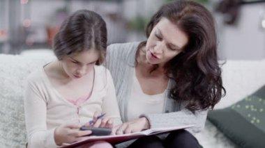 Madre aiuta la figlia a fare i compiti — Video Stock