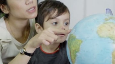 Mother using a globe to educate her young son — Stock Video