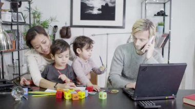A busy father is working from home while his wife entertains their children — Stock Video