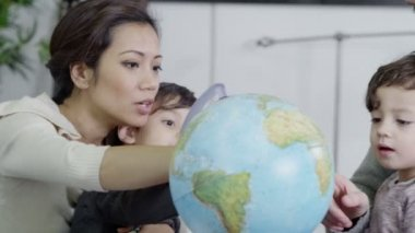 Attractive young parents using a globe to educate their children — Stock Video