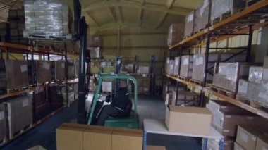 Worker uses forklift truck to move stacks of boxes — Stock Video