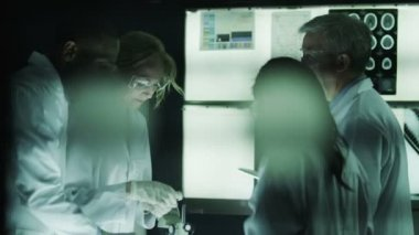Scientists working in dark laboratory — Vídeo de Stock