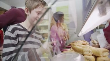 Cute and happy little boy choosing a fresh savory pastry at the bakery counter — Stok video