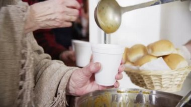 Feeding the hungry - eager hands take soup and bread — Stock Video