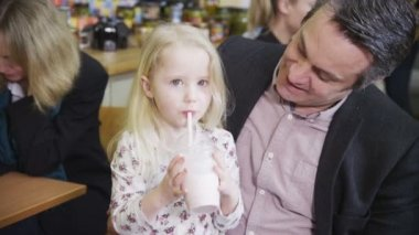 Cute little girl in a cafe enjoys sharing her milkshake — Stock Video