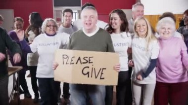 Large group of charity volunteers smile into camera holding a Please Give sign — Stock Video