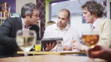 Three cheerful businessmen in casual meeting in a cafe — Stock Video