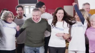 Large group of charity volunteers embrace and give big smiles into camera — Stock Video