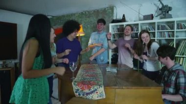 Happy and carefree group of young friends gathered around a piano at a party — Stock Video