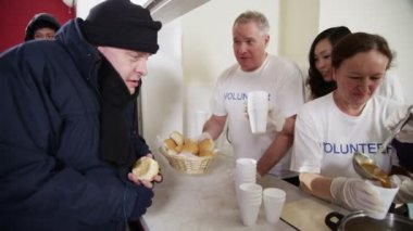 Soup kitchen volunteers help to feed the homeless — Stock Video