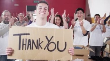 Charity worker holds up a Thank you sign as his fellow workers applaud — Stock Video