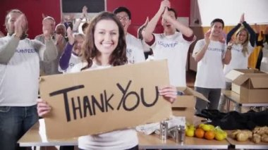 Charity worker holds up a Thank you sign as her fellow workers applaud — Stock Video