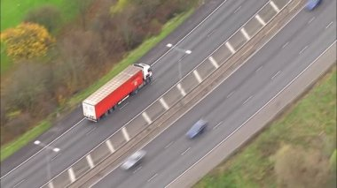 Aerial view of a truck and other traffic driving on the outskirts of a city — Stock Video