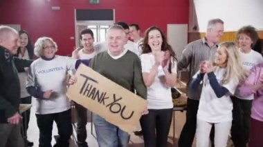 Large group of charity volunteers smile into camera holding a Thank You sign — Stock Video