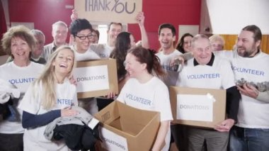 Happy group of fundraisers holding donated goods and a Thank You sign — Stock Video