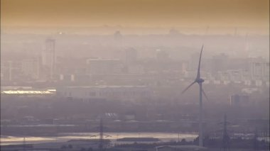 Aerial view of wind turbines set against the hazy smog of a large city — Stock Video