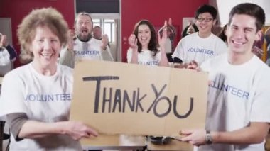 Two Charity workers hold up a Thank you sign as their fellow workers applaud — Stock Video