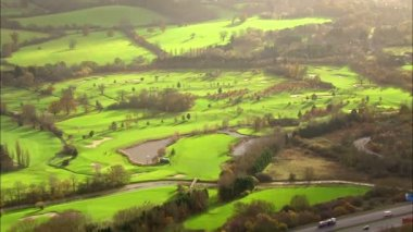 Aerial view over a golf course set in the English countryside — Stock Video