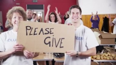 Two Charity workers hold up a Please Give sign as their fellow workers applaud — Stock Video