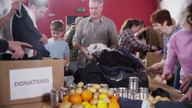 Charity volunteers and community members sorting through donated goods — Stock Video
