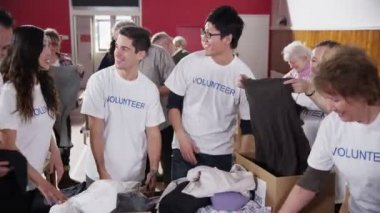 Charity volunteers have fun together as they sort through donated goods — Stock Video