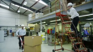 Staff members in a busy warehouse, each carrying out their own roles — Stockvideo