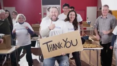 Group of charity volunteers give thumbs up to camera with a Thank You sign — Stock Video