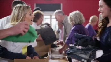 Charity workers accepting donations of food and clothing from community members — Stock Video
