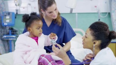 Female doctor uses a stethoscope to examine cute little girl in hospital. — Stock Video