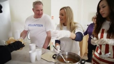 Soup kitchen volunteers help to feed the homeless — Vídeo Stock