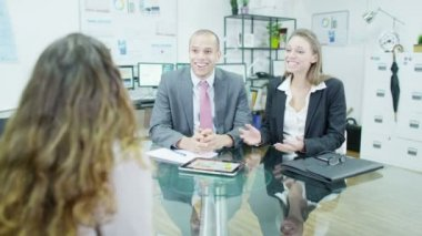 Lady boss gives good news to two of her staff in a business meeting — Stock Video