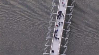 Aerial view of pedestrians crossing London's Millennium bridge — Stock Video