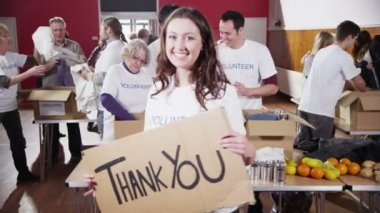 Beautiful female charity worker holds up a Thank you sign to camera — Stock Video