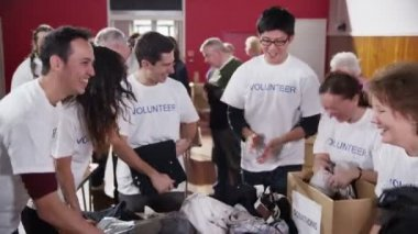 Charity volunteers have fun together as they sort through donated clothing — Vídeo Stock