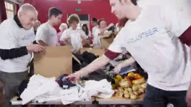 Large group of charity volunteers sorting through donated goods — Stock Video