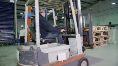 Team of busy warehouse workers lifting and moving empty wooden pallets — Stock Video