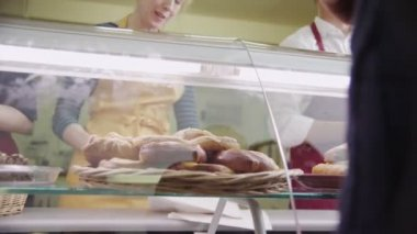 Friendly staff serving customers with a smile at the bakery counter — Stock Video