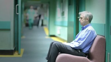 Worried man sits in hospital waiting area — Stock Video