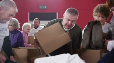 Charity workers and community members sort through piles of donated clothing — Vídeo Stock